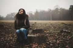 Young woman sitting tree trunk stock images