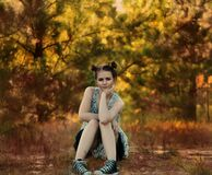 Young woman sitting beside trees in Autumn stock photo