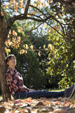 Young woman sitting under autumn tree leaning on its trunk Stock Photo