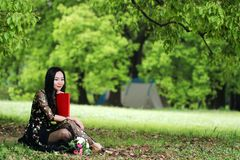 Read a book sitting under a blossom tree stock photos
