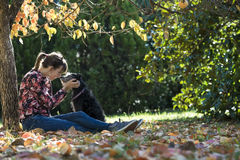 Young woman sitting under a coulourful autum tree lovingly petti Stock Photos