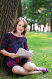 Young woman sitting under a tree Stock Photos