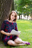 Young woman sitting under a tree Royalty Free Stock Photography