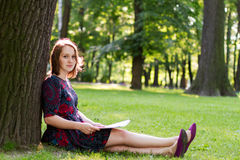 Young woman sitting under a tree Royalty Free Stock Photos