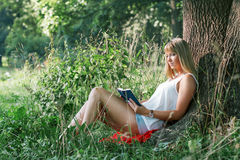 Young woman sitting under a tree and reading a book Royalty Free Stock Photography