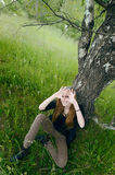 Young woman sitting under tree Stock Photo
