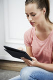 Young woman sitting and using digital tablet Royalty Free Stock Photography