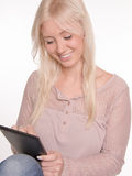 Young woman sitting using tablet Stock Images