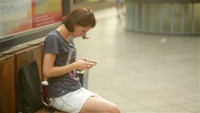 Young woman sitting in waiting on the bench in the railway station, holding smartphone, looking at screen, using cell stock footage