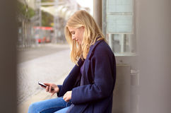 Young woman sitting waiting for a bus Stock Photos