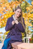 Young woman sitting on a wall in fall park Stock Images