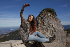 Young woman sitting on a wall and shooting a selfie Stock Photography