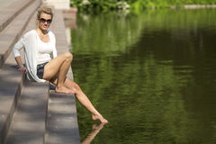 Young  woman sitting on the waterfront pulls leg to water. Stock Image