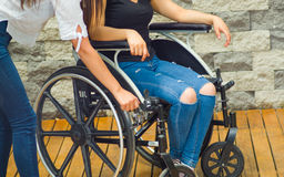 Young woman sitting in wheelchair with assistant standing next to her, both smiling happily showing positive attitude Stock Images