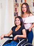 Young woman sitting in wheelchair with assistant standing next to her, both smiling happily showing positive attitude Royalty Free Stock Photography