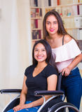 Young woman sitting in wheelchair with assistant standing next to her, both smiling happily showing positive attitude Royalty Free Stock Photo
