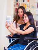 Young woman sitting in wheelchair using mobile with assistant standing next to her, both smiling happily showing Royalty Free Stock Photos