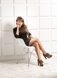 Young woman sitting on white chair at studio against bricked wal Royalty Free Stock Images
