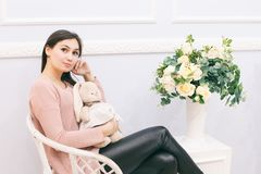 Young woman sitting on wicker chair at home. Bouquet of flowers near chair stock photography