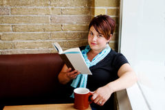 Young woman sitting by window in cafe Stock Image