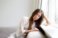 Young woman sitting by window at home Royalty Free Stock Photos