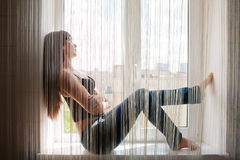 Young woman sitting on window sill. Portrait of young woman sitting on window sill. Profile view Royalty Free Stock Photos