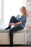 Young woman sitting on windowsill Stock Photos