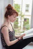 Young woman sitting on a windowsill reading Stock Photo