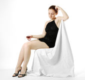 Young woman sitting with wineglass edgeways. Adult girl sits in black short cocktail dress and holds glass with wine sidelong on light background, gaze lowered Royalty Free Stock Photo