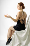 Young woman sitting with wineglass, half-turn. Adult girl sits in black short cocktail dress and holds glass with wine, half-face, long red hair arranged back of Royalty Free Stock Photography