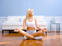 Young Woman Sitting on Wood Floor Meditating Royalty Free Stock Photos