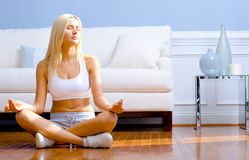 Young Woman Sitting on Wood Floor Meditating Royalty Free Stock Images