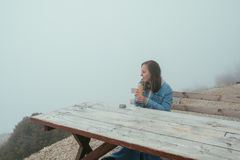 Young woman sitting on Wooden bench and drinking hot tea from a Stock Photo