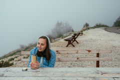 Young woman sitting on Wooden bench and drinking hot tea from a Royalty Free Stock Photo