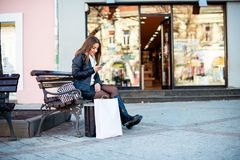 Young girl text messaging after shopping Royalty Free Stock Photo