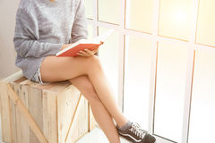 Young woman sitting on the wooden chair reading book near the wi. Ndows Stock Photos