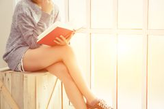 Young woman sitting on the wooden chair reading book near the  w. Indows background Royalty Free Stock Photo