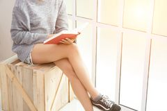 Young woman sitting on the wooden chair reading book near the wi. Ndows Royalty Free Stock Photos