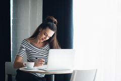 Young woman is sitting at wooden desk near window and making notes. Adult attractive female is sitting with a laptop and Royalty Free Stock Photography