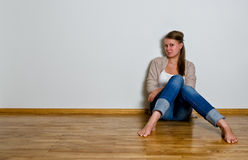 Young woman sitting on the wooden floor Royalty Free Stock Photos