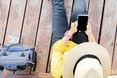 Young woman sitting on the wooden floor with mobile phone royalty free stock image