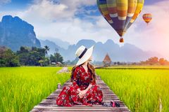 Young woman sitting on wooden path and look at balloons with green rice field in Vang Vieng, Laos Stock Image