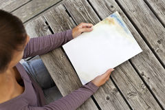 Young woman sitting at wooden table with a booklet with white Cover Stock Images