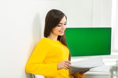 Young woman sitting at workplace and reading paper in office. On the background is a green screen.  royalty free stock photography