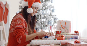 Young woman sitting wrapping Christmas gifts Royalty Free Stock Images