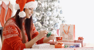 Young woman sitting wrapping Christmas gifts Stock Image