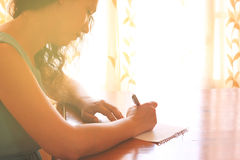 Young woman sitting and writing letter near bright window light. filtered image. Royalty Free Stock Photo
