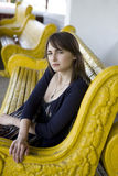 Young woman sitting on yellow bench Royalty Free Stock Photography