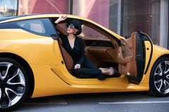 Young woman sitting in a yellow sports car. Happy beautiful young woman sitting in a yellow sports car on beautiful sunny summer day. Business Woman lady in Stock Photos