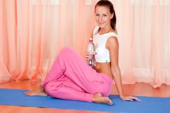 Young woman sitting on a yoga mat Stock Photo